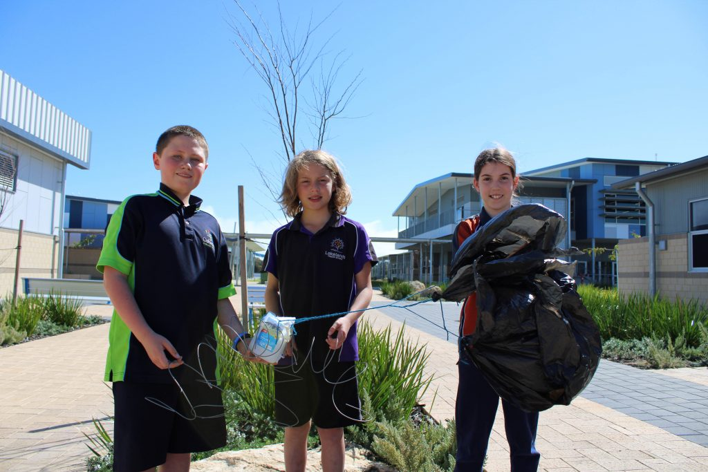 3 Year 4 Students, Tane, Mackenzie and Daniel, holding their luna lander. A milk carton with springs and a parachute made from a plastic bin bag.