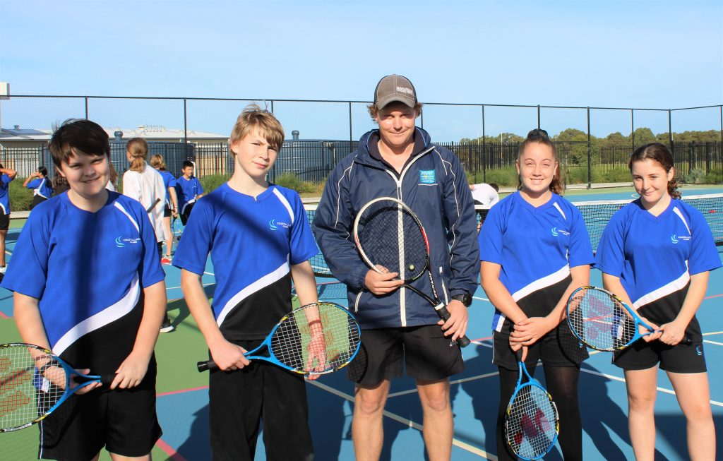 4 Coastal Lakes College students standing on a tennis court with a tennis coach