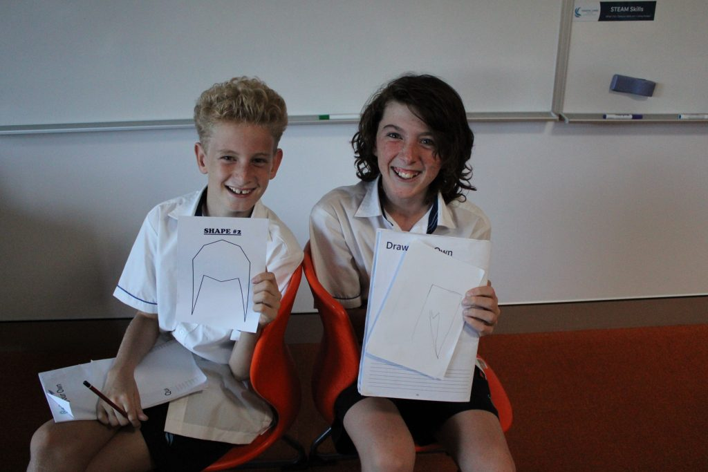 Two boys looking at the camera, showing their drawings and laughing at each other
