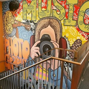 part of a wall mural showing a girl holding a camera