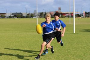 Two boys chasing down a footy