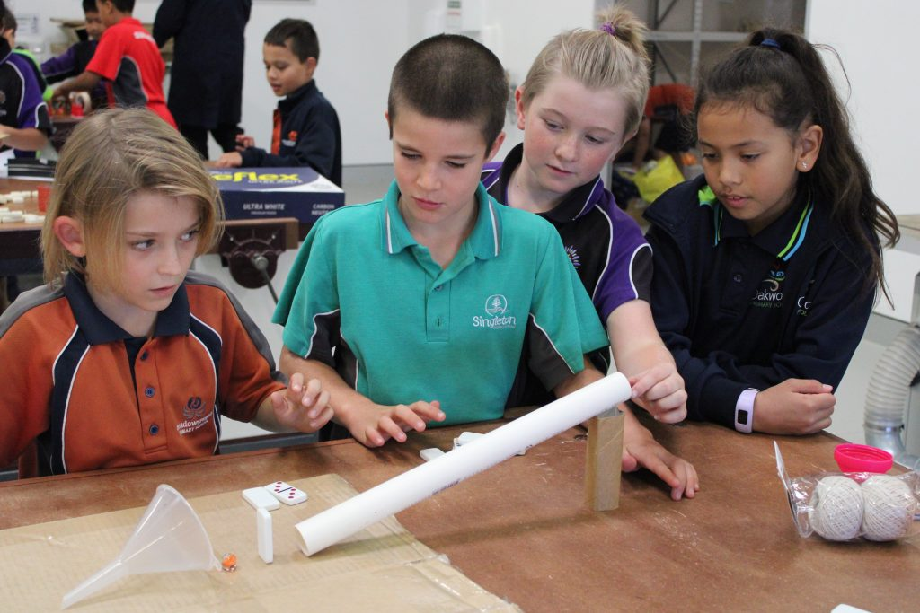 4 Year 4 students from local primary schools putting a marble down a pipe
