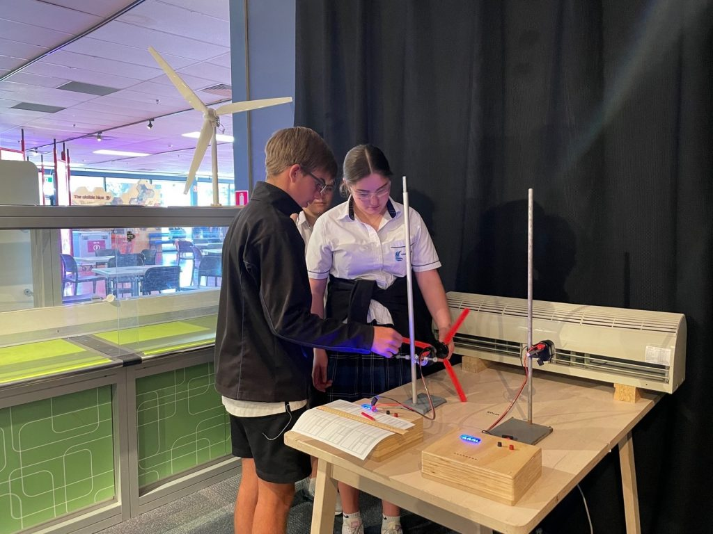 two students playing with a motorised propella